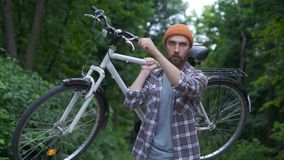 Brutal hipster guy in park carrying fixie bicycle. Hipster guy in town carrying fixie bicycle stock video footage