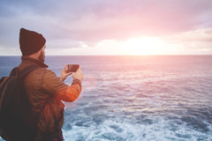 Hipster guy with trendy look shoots video with ocean landscape on mobile phone Royalty Free Stock Photo