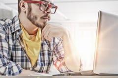 Hipster guy use laptop . Mixed media Stock Image