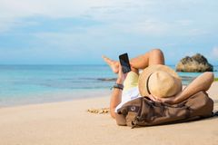 Guy with smartphone lying on the beach. Hipster guy using smartphone while lying on the beach stock photos
