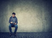 Hipster guy using tablet sitting on chair. Stylish young man sitting on chair and browsing tablet with confidence on gray wall background Stock Image