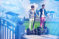 Hipster guys enjoy outdoors on the segway. Hipster guys enjoy outdoors in the house yard on the segway Royalty Free Stock Images