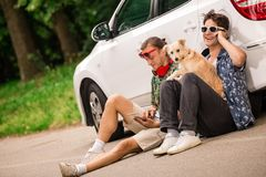 Fashionable men and dog on the road travel summer vacation concept. Hipster guys and their dog sitting next to car on the road and using mobile phone and tablet stock images