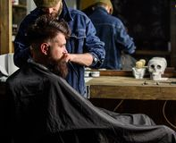 Hipster hairstyle concept. Hipster client getting haircut. Barber with hair clipper works on haircut of bearded guy. Mirror background. Barber with clipper royalty free stock photo
