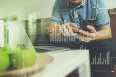 Hipster hand using laptop compter and mobile payments online bus. Iness,omni channel,sitting on sofa in living room,green apples in wooden tray,graphic interfce Royalty Free Stock Image