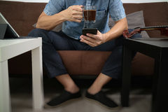Hipster hand using smart phone,digital tablet docking keyboard,c. Offee cup, payments online business,sitting on sofa in living room,work at home concept Stock Photography