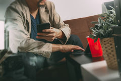Hipster hand using smart phone,digital tablet docking keyboard,c. Offee cup, payments online business,sitting on sofa in living room,work at home concept,filter Royalty Free Stock Photos