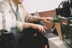 Hipster hand using smart phone,digital tablet docking keyboard,coffee cup, payments online business,sitting on sofa in living. Room,work at home concept royalty free stock images