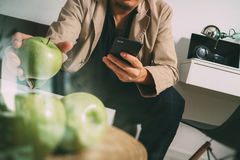 Hipster hand using smart phone for mobile payments online busine. Ss,sitting on sofa in living room,holding green apple in wooden tray,filter Stock Photo