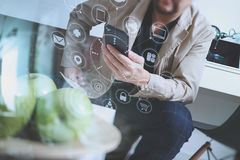 Hipster hand using smart phone for mobile payments online busine. Ss,sitting on sofa in living room,holding green apple in wooden tray,virtual computer interface Royalty Free Stock Photos