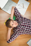 Hipster with hands behind head lying on hardwood floor Royalty Free Stock Photos