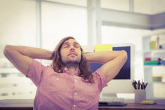 Hipster with hands behind head resting at computer desk Stock Image