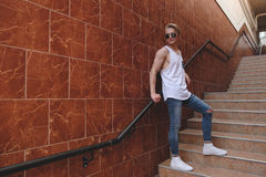 Hipster handsome blonde man guy in stylish summer clothes in the street. Hipster handsome man guy in stylish summer clothes in the street in sunglasses Royalty Free Stock Photography