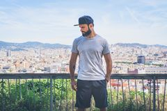 Hipster handsome male model with beard wearing gray blank t-shirt and a black snapback cap with space for your logo or. Design in casual urban style.Panoramic Stock Image