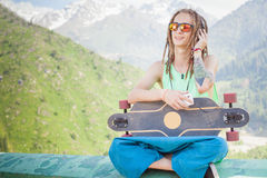 Hipster handsome man with skateboard and mobilephone listening to music Royalty Free Stock Photos