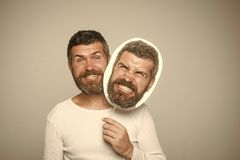 Hipster with happy and angry face hold portrait nameplate. stock photo