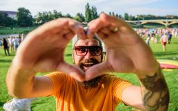 Hipster happy celebrate event picnic fest festival. Cheerful fan love summer fest. Man bearded hipster in front of crowd. People show heart gesture riverside stock image