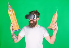 Hipster on happy face study architecture in virtual reality. Guy in VR glasses hold in hands Big Ben and Empire State stock photography