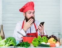 Hipster in hat and apron learning how cook online. Culinary education online. Elearning concept. Man chef searching. Internet recipe cooking food. Chef stock image