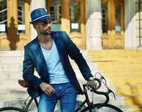 Hipster in hat and sunglasses with bicycle in city Royalty Free Stock Image