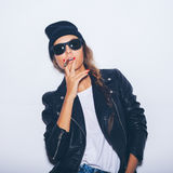 Hipster haughty girl in sunglasses and black leather jacket smoking cigar Royalty Free Stock Photo