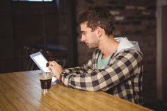 Hipster having coffee and using tablet computer Royalty Free Stock Image