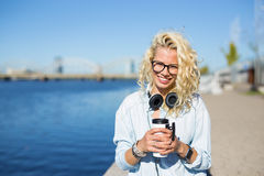 Hipster with headphones around neck and coffee cup in hands Royalty Free Stock Photography
