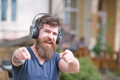Hipster with headphones on happy face listening music and pointing forward. Music lover concept. Hipster with long beard. And mustache with wireless headphones royalty free stock images