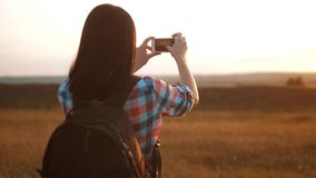 Hipster hiker silhouette girl is shooting video of beautiful nature sundown on cell telephone smartphone slow motion. Video. Female tourist taking photo with stock footage
