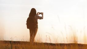 Hipster hiker silhouette girl is shooting video of beautiful nature sundown on cell telephone smartphone slow motion. Hipster hiker silhouette girl shooting stock video