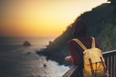 Hipster hiker tourist with backpack looking of amazing seascape sunset on background blue sea, girl enjoying ocean horizon, royalty free stock photo