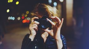 Hipster hiker tourist making photo, holding in hands camera on background of evening atmospheric city, photographer girl enjoying. Night street in trip stock photo