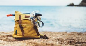 Hipster hiker tourist yellow backpack and swimming mask on background blue sea ocean horizon on sand beach, blurred panoramic seas. Cape blank, traveler relax stock image