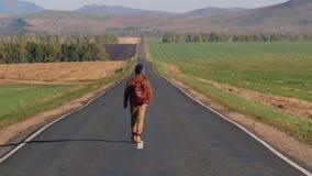 Hipster hitchhiker tourist traveler man walking along long road, hitchhiking summer