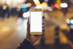 Hipster hold in hands clean gadget mobile phone closeup, blank screen smartphone on background bokeh light in night. Atmospheric city, mockup street, lifestyle royalty free stock photos