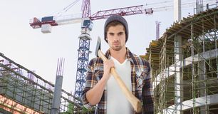 Hipster holding ax against incomplete buildings and crane Stock Images