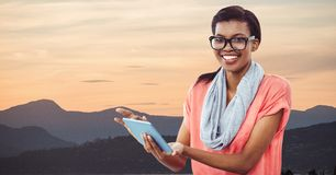 Hipster holding digital tablet while standing by mountains against sky stock photography