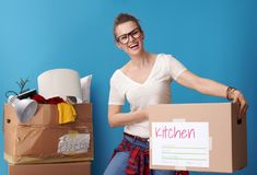 Hipster holding signed box and with untidy box in background Stock Image