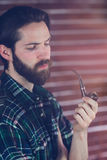Hipster holding smoking pipe Stock Photo