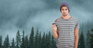 Hipster holding smoking pipe against fog covering forest. Digital composite of Hipster holding smoking pipe against fog covering forest Stock Images