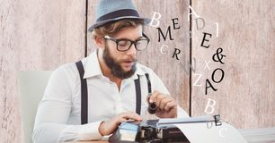 Hipster holding smoking pipe while using typewriter. Digital composite of Hipster holding smoking pipe while using typewriter Stock Image