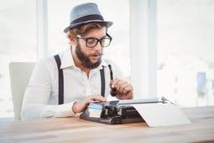 Hipster holding smoking pipe while working on typewriter Royalty Free Stock Image