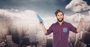 Hipster holding tablet PC against cityscape. Digital composite of Hipster holding tablet PC against cityscape royalty free stock images