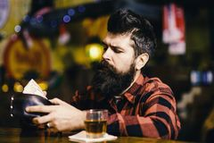Hipster holds wallet, counting money to buy drinks. Depression and alcoholism concept. Guy spend leisure in bar royalty free stock photography