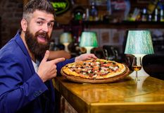 Hipster hungry eat italian pizza. Pizza favorite restaurant food. Fresh hot pizza for dinner. Hipster client sit at bar royalty free stock image