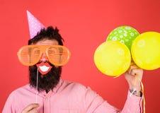 Hipster i jätte- fira för solglasögon Grabben i partihatt med luftballonger firar Begrepp för fotobåsgyckel man arkivbilder