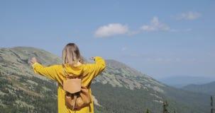 Hipster jong meisje die met rugzak van mening over piek van berg genieten stock video
