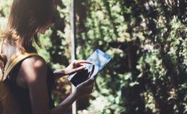 Hipster jong meisje met rugzak die tabletcomputer, handen met behulp van die gadget houden en bericht op apparaat texting De reiz stock foto