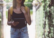 Hipster jong meisje met rugzak die tabletcomputer, handen met behulp van die gadget houden en bericht op apparaat texting De reiz stock foto's