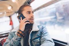 Hipster jonge mannelijke bespreking telefonisch in bus royalty-vrije stock fotografie